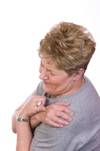 flu like symptoms, woman holding sore shoulders